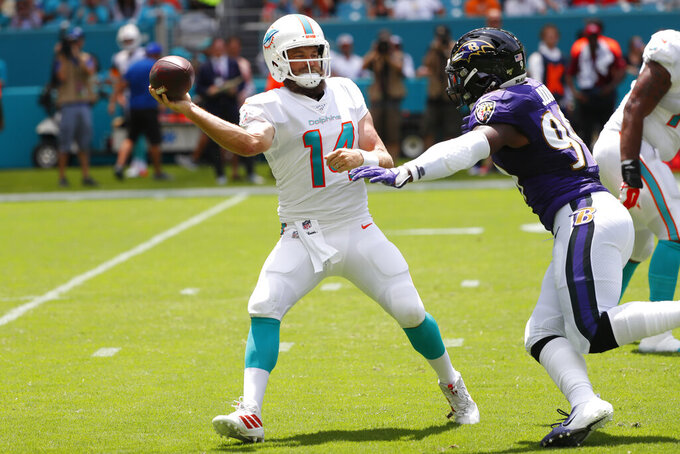 Miami Dolphins quarterback Ryan Fitzpatrick (14) looks to pass under pressure from Baltimore Ravens outside linebacker Matt Judon (99), during the first half at an NFL football game Sunday, Sept. 8, 2019, in Miami Gardens, Fla. (AP Photo/Wilfredo Lee)