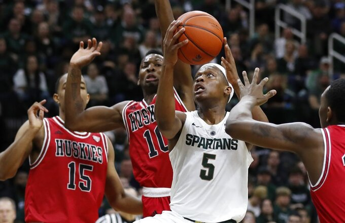 Michigan State guard Cassius Winston (5) makes a layup as Northern Illinois defends during the second half of an NCAA college basketball game, Saturday, Dec. 29, 2018, in East Lansing, Mich. (AP Photo/Carlos Osorio)