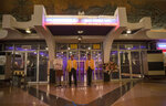 Cinema ushers wear face shields stand outside the entrance to the Scala theater Friday, July 3, 2020 in Bangkok, Thailand. The Scala theater has shut its doors after 51 years as a shrine for Thai movie-goers. (AP Photo/Sakchai Lalit)