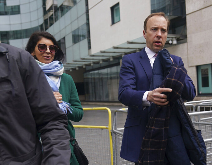 """In this photo taken on May 16, 2021, Britain's Health Secretary Matt Hancock, right walks with aide Gina Coladangelo, outside BBC Broadcasting House in London after his appearance on the BBC1 current affairs programme, The Andrew Marr Show. Hancock has apologized for breaching social distancing rules after a newspaper ran pictures of him embracing a woman with whom he allegedly had an affair. Health Secretary Matt Hancock said in a statement that """"I accept that I breached the social distancing guidance in these circumstances."""" He said """"I have let people down and am very sorry."""" The tabloid Sun newspaper reported Friday, June 25, 2021 that Hancock had an extramarital affair with a senior aide, Gina Coladangelo. (Yui Mok/PA via AP)"""