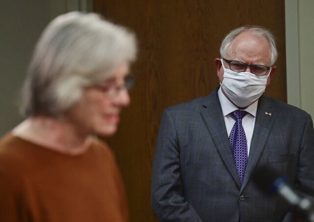 Minnesota Gov. Tim Walz, right, listens to Minnesota Health Commissioner Jan Malcolm as she provides an update on the state's response to the coronavirus pandemic, during a news conference in St. Paul, Minn., Wednesday, May 27, 2020. (John Autey/Pioneer Press via AP, Pool)