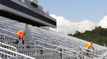 Cleaners, who will be working during the race, clean handrails during a walkthrough at the New Hampshire Motor Speedway, Friday, July 31, 2020, in Loudon, N.H., in preparation for this Sunday's Foxwoods 301 NASCAR auto race. (AP Photo/Charles Krupa)