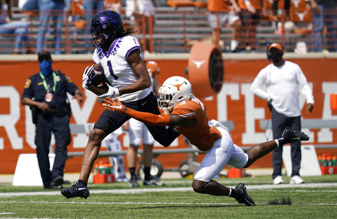 TCU wide receiver Quentin Johnston (1) reaches for a pass over Texas defensive back Jalen Green (3) during the first half of an NCAA college football game, Saturday, Oct. 3, 2020, in Austin, Texas. Johnston was tripped up on the play and dropped the ball. (AP Photo/Eric Gay)