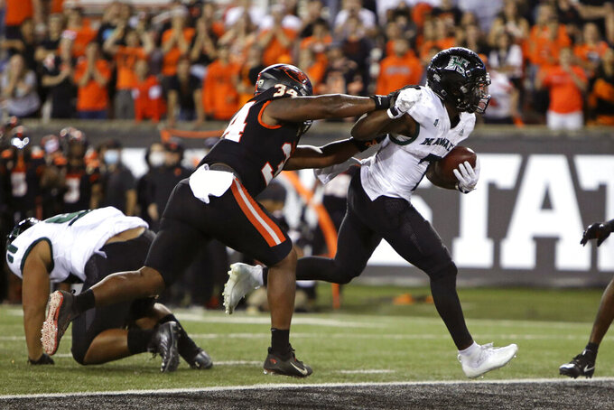 Hawaii running back Calvin Turner Jr. (7) slips past Oregon State inside linebacker Avery Roberts (34) to score a touchdown during the second half of an NCAA college football game Saturday, Sept. 11, 2021, in Corvallis, Ore. Oregon State won 45-27. (AP Photo/Amanda Loman)