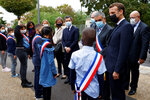 French President Emmanuel Macron, right, wearing a protective face mask speaks to youngsters standing in line outside the 'la Maison des habitants' (MDH) in Les Mureaux, northwest of Paris, Friday, Oct. 2, 2020. President Emmanuel Macron, trying to rid France of what authorities say is a