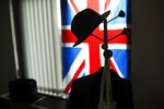 A hat hangs on a coat stand in front of the Union flag in the office of British European Parliament member Nigel Farage at the European Parliament in Brussels, Tuesday, Jan. 28, 2020. With the Brexit moment set for Friday at midnight Brussels time, UK parliamentarians are packing boxes and removing personal items from their Brussels offices. (AP Photo/Francisco Seco)
