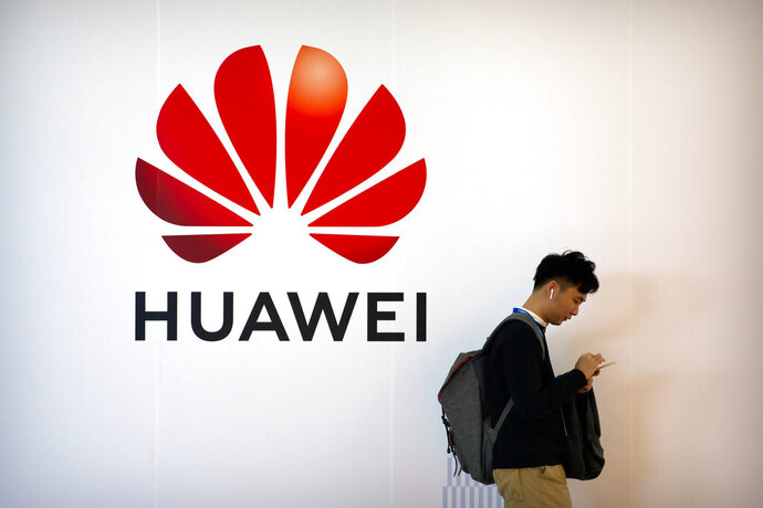 FILE - In this Oct. 31, 2019, file photo, a man uses his smartphone as he stands near a billboard for Chinese technology firm Huawei at the PT Expo in Beijing. Huawei Technologies reported Tuesday, July 14, 2020, that its revenue grew 13.1% in the first half of the year compared with a year earlier, despite sanctions from the U.S and challenges from the coronavirus pandemic.(AP Photo/Mark Schiefelbein, File)