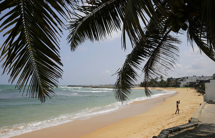 In this May 10, 2019 file photo, a boy walks on a beach in Hikkaduwa, Sri Lanka. Sri Lanka's government says it will decrease ground handling charges for airlines and slash aviation fuel and embarkation taxes to help the country's vital tourism industry recover after the Easter attacks that killed more than 250 people. (AP Photo/Eranga Jayawardena, File)