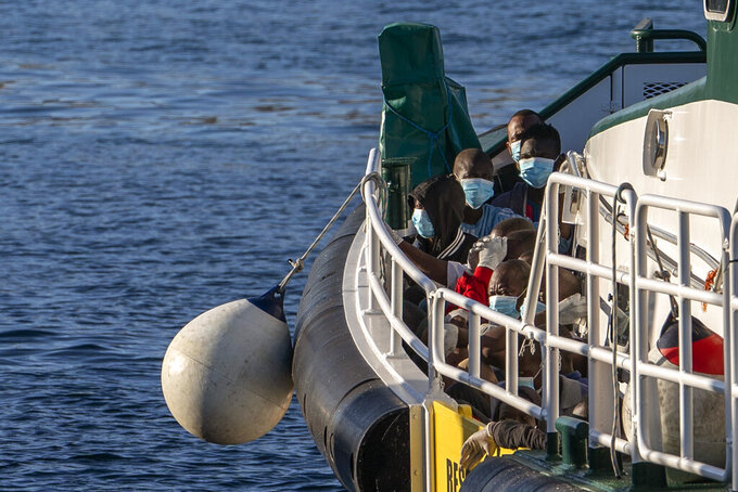Migrants wearing face masks sit on the deck of a police rescue boat as they arrive at the Arguineguin port in Gran Canaria island, Spain, after being rescued in the Atlantic Ocean on Thursday, Aug. 20, 2020. More than 250 people are known to have died or gone missing in the Atlantic route so far this year. (AP Photo/Emilio Morenatti)