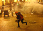 An anti-government protester runs after he throws stones against the riot police, background, during a protest near the parliament square, in downtown Beirut, Lebanon, Sunday, Dec. 15, 2019. Lebanese security forces fired tear gas, rubber bullets and water cannons Sunday to disperse hundreds of protesters for a second straight day, ending what started as a peaceful rally in defiance of the toughest crackdown on anti-government demonstrations in two months. (AP Photo/Hussein Malla)