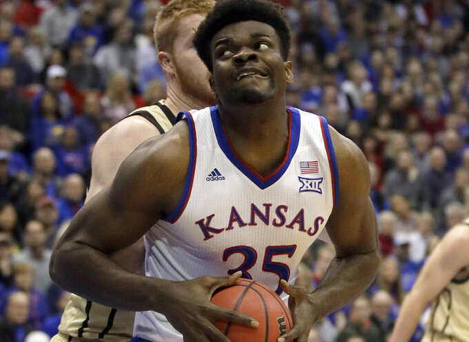 FILE - In this Dec. 4, 2018, file photo, Kansas center Udoka Azubuike (35) drives to the basket past Wofford center Matthew Pegram, back, during the first half of an NCAA college basketball game in Lawrence, Kan. The University of Kansas and Adidas announced Wednesday, April 24, 2019, an extension of their contract through 2031, despite an FBI investigation centered on the footwear and apparel company that cast a negative light on the Jayhawks' athletic programs. The Jayhawks have worn Adidas gear since 2005. The original eight-year agreement was extended by six years through 2019, then another extension was put on hold last fall amid the investigation. The new deal is worth $14 million annually. (AP Photo/Orlin Wagner, File)