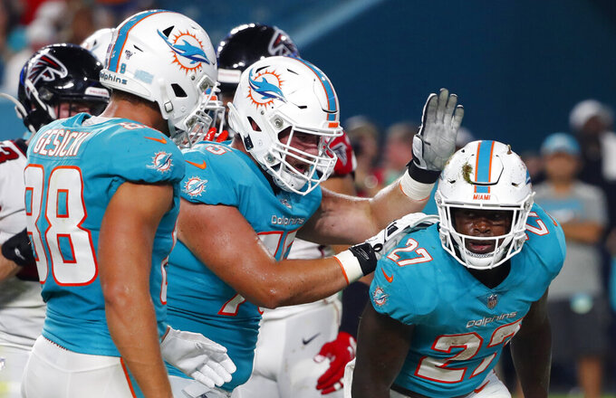 Miami Dolphins running back Kalen Ballage (27) is congratulated by offensive lineman Will Holden, center, after scoring a touchdown against the Atlanta Falcons during the first half of a preseason NFL football game Thursday, Aug. 8, 2019, in Miami Gardens, Fla. (AP Photo/Wilfredo Lee)