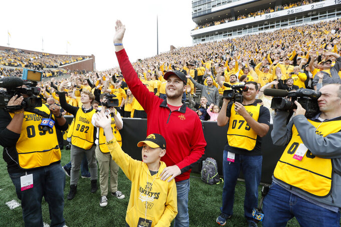 FILE - In this Sept. 28, 2019, file photo, Carson King, of Altoona, Iowa, center in red, waves to patients in the University of Iowa Stead Family Children's Hospital at the end of the first quarter of an NCAA college football game between Iowa and Middle Tennessee, in Iowa City, Iowa. King raised almost $3 million for the University of Iowa Stead Family Children's Hospital after his decision to display a hand-written sign before the Sept. 14 Iowa State-Iowa football game seeking money for beer prompted an overwhelming number of donations. (AP Photo/Charlie Neibergall, File)