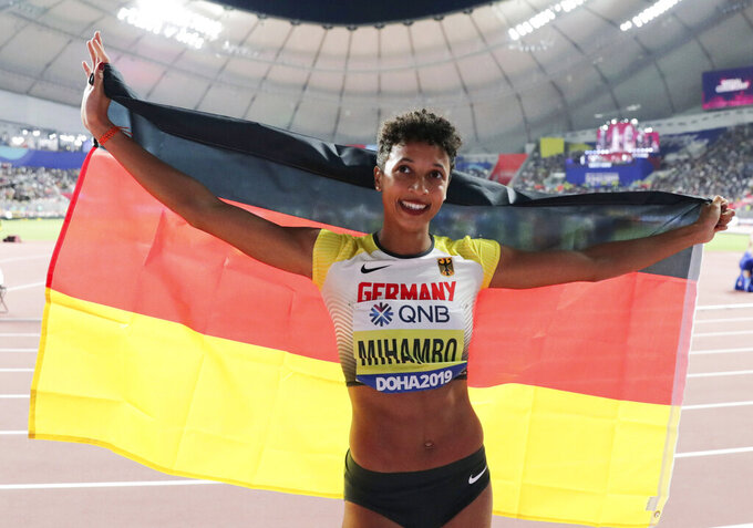 """FILE - In this Sunday, Oct. 6, 2019 file photo, Malaika Mihambo, of Germany, celebrates her gold medal in the women's long jump final at the World Athletics Championships in Doha, Qatar. World long jump champion Mihambo wants to double up with the 100 meters at the Tokyo Olympics next summer. """"That's definitely the plan for next year. I've noticed that I really like sprinting,"""" Mihambo told German news magazine Der Spiegel in an interview published Saturday, Nov. 21, 2020 but said it would be tough to establish herself as a sprinter. (AP Photo/Hassan Ammar, file)"""