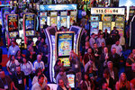 People stand among electronic slot machines at the IGT booth during the Global Gaming Expo, Wednesday, Oct. 10, 2018, in Las Vegas. (AP Photo/John Locher)