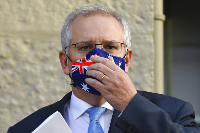 Australian Prime Minister Scott Morrison adjusts his mask during the announcement of a COVID-19 financial support package in Sydney, Tuesday, July 13, 2021. Morrison announced added financial support for businesses and households as Sydney appears increasingly likely to enter a fourth week of lockdown due to coronavirus clusters. (Mick Tsikas/AAP Image via AP)