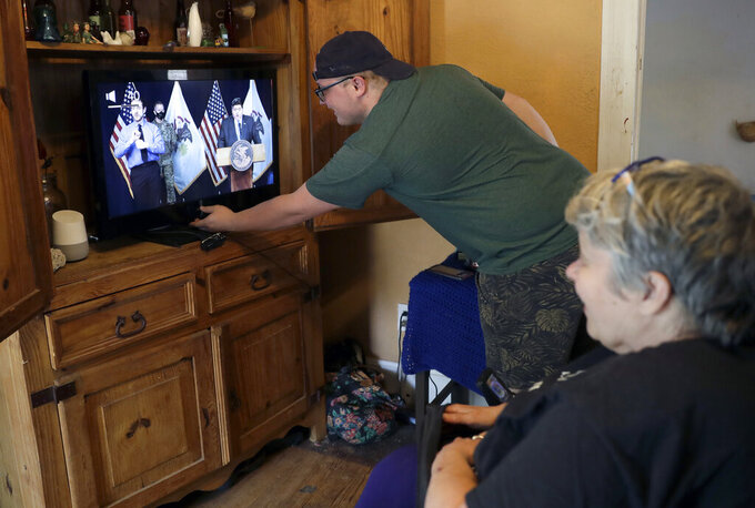 File - Zach Stafford adjusts the volume as he and his mother, Debra Mize, right, watch a livestream of the daily coronavirus briefing by Illinois Gov. J.B. Pritzker on a television inside their home on April 28, 2020, in Belleville, Ill. Television networks are grumbling that the Nielsen company is not accurately measuring how many people are watching their programs. Networks believe that it's counter-intuitive that fewer people are watching TV at a time the pandemic is keeping so many at home. Nielsen says that after an initial burst of interest last spring, long-term trends taking people away from TV have re-emerged, including increased numbers of people spending time on their devices, or listening to podcasts. (AP Photo/Jeff Roberson)