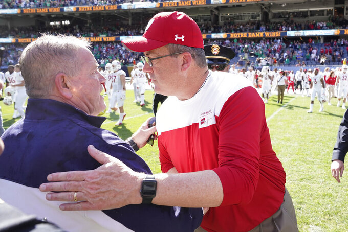 Notre Dame head coach Brian Kelly, left, and Wisconsin head coach Paul Chryst meet after an NCAA college football game Saturday, Sept. 25, 2021, in Chicago. Notre Dame won 41-13(AP Photo/Charles Rex Arbogast)