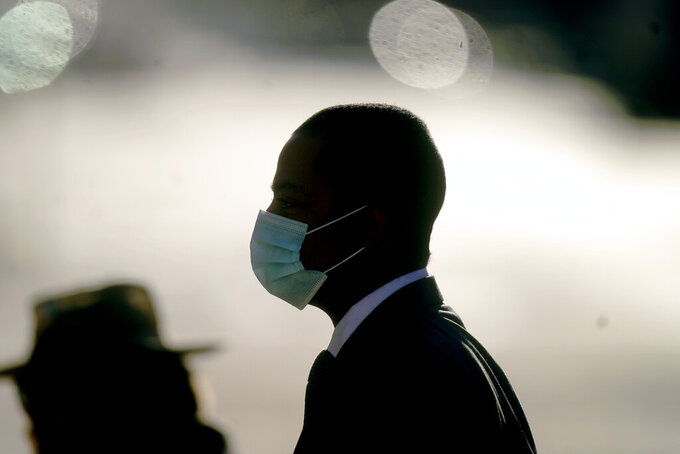 FILE - In this April 1, 2021 file photo a man walks in downtown Salt Lake City. Utah will become the latest state to lift its mask mandate on Saturday, April 10, 2021, under a new state law, but the capital city and many businesses will continue requiring masks amid concern about communities still vulnerable to the coronavirus pandemic. (AP Photo/Rick Bowmer,File)