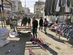 People and security forces gather at the site of a deadly bomb attack in Baghdad's bustling commercial area, Iraq, Thursday, Jan. 21, 2021. Twin suicide bombings hit Iraq's capital Thursday killing and wounding civilians, police and state TV said. (AP Photo/Hadi Mizban)
