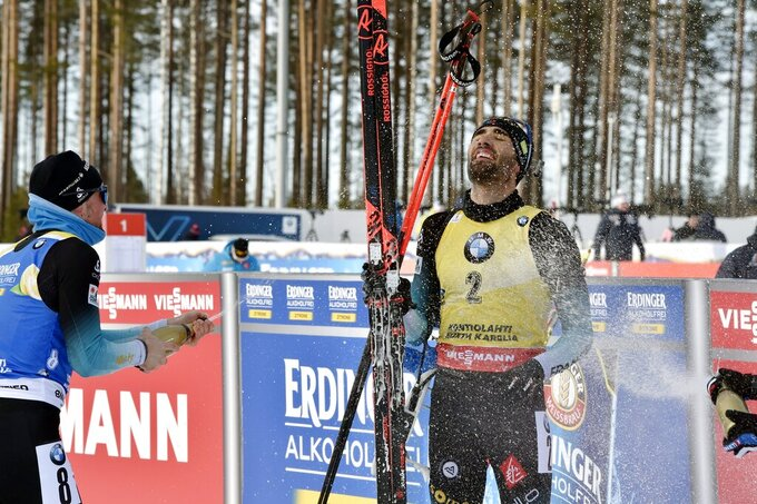 Simon Desthieux, left, of France sprays champagne at Martin Fourcade of France who celebrates victory and the end of career after winning the men's 12.5 km Pursuit competition at the IBU Biathlon World Cup in Kontiolahti, Finland, on Saturday March 14, 2020.  Fourcade ends his career after today's competition that ends the season, exactly ten years after he took his first World Cup victory in Kontiolahti. (Jussi Nukari/Lehtikuva via AP)