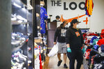 Roni Colvert, center, makes a purchase after selecting her goods through the front door from curb-side at The Loop fashion and shoe store as businesses slowly begin to reopen after social distancing restrictions shuttered storefronts nationwide, Tuesday, May 26, 2020, in Yonkers, N.Y. (AP Photo/John Minchillo)