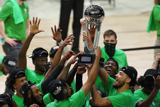 North Texas players celebrate with the trophy after the championship game against Western Kentucky in the NCAA Conference USA men's basketball tournament Saturday, March 13, 2021, in Frisco, Texas. North Texas won 61-57 in overtime. (AP Photo/Tony Gutierrez)