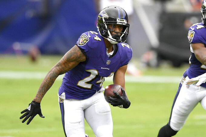 Baltimore Ravens cornerback Marcus Peters (24) runs with the ball after intercepting a pass from Cincinnati Bengals quarterback Joe Burrow during the first half of an NFL football game, Sunday, Oct. 11, 2020, in Baltimore. (AP Photo/Nick Wass)