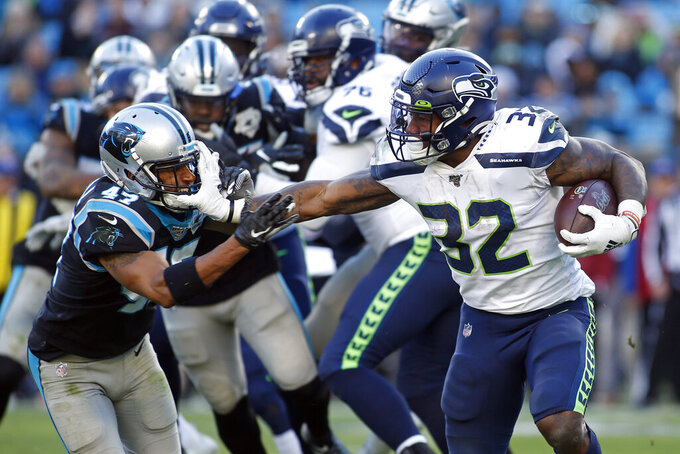 Seattle Seahawks running back Chris Carson (32) runs while Carolina Panthers defensive back Ross Cockrell (47) chases during the second half of an NFL football game in Charlotte, N.C., Sunday, Dec. 15, 2019. (AP Photo/Brian Blanco)