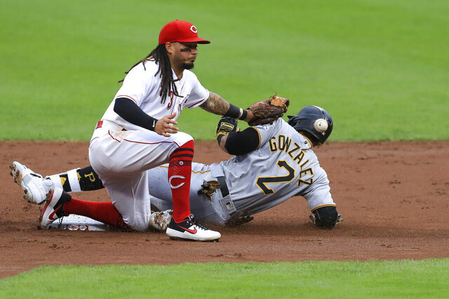 Cincinnati Reds' Freddy Galvis (3) attempts to field the ball as Pittsburgh Pirates' Erik Gonzalez (2) is safe after hitting a double in the second inning during a baseball game at in Cincinnati, Friday, Aug. 14, 2020. (AP Photo/Aaron Doster)