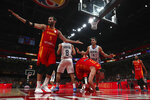 Spain's Marc Gasol center tumbles as teammate Rudy Fernandez, at left, and Argentina's Luis Scola, center in white, react during the final of the FIBA Basketball World Cup held at the Cadillac Arena in Beijing, Sunday, Sept. 15, 2019. (AP Photo/Ng Han Guan, Pool)