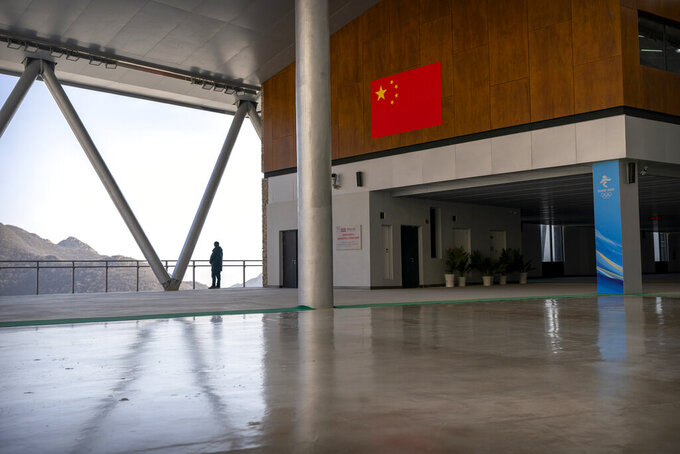 A staff member stands at a balcony near a Chinese flag at the National Sledding Center in Yanqing on the outskirts of Beijing, Friday, Feb. 5, 2021. Beijing Olympic organizers showed off the downhill skiing venue and the world's longest bobsled and luge track Friday, one year ahead of the scheduled opening of the 2022 Olympic Winter Games. (AP Photo/Mark Schiefelbein)