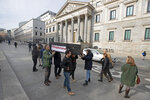 Protesters from the pro-life group Derecho a Vivir carry a mock coffin outside the Spanish parliament in Madrid, Spain, Tuesday, Feb. 11, 2020. Spain's new parliament is expected to accept in its first legislative session a majority vote the debate on a law that decriminalizes and regulates euthanasia. (AP Photo/Paul White)