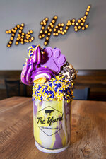 Tiger Deaux,' is one of gourmet milkshakes at The Yard Milkshake Bar, Tuesday, July 13, 2021 in Baton Rouge, La. It's a tip of the hat to LSU fans, and it features Cookie Dough ice cream with LSU purple and gold marshmallow cream, topped with purple and gold whipped cream, a scoop of chocolate chip cookie dough, more Tiger Sprinkles and a purple Tiger Paw. (Travis Spradling/The Advocate via AP)