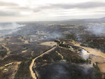 In this Monday, Dec. 30, 2019, aerial photo, acres of scorched land are seen in Bairnsdale, Australia. Thousands of tourists fled Australia's wildfire-ravaged eastern coast Thursday ahead of worsening conditions as the military started to evacuate people trapped on the shore further south. (Glen Morey via AP)