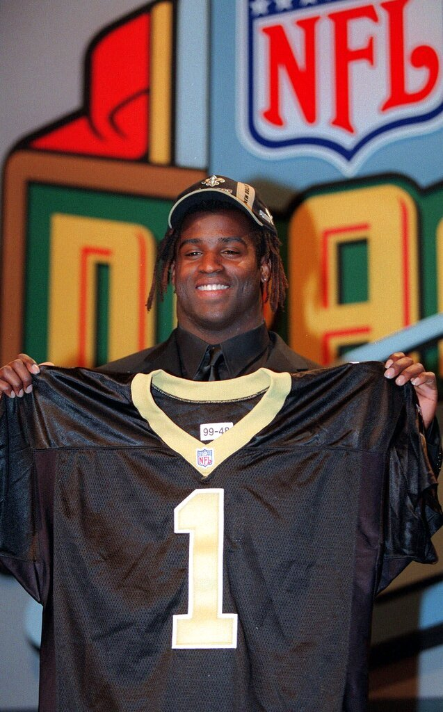 FILE - In this April 17, 1999, file photo, Texas running back Ricky Williams poses with a New Orleans Saints jersey after the Saints made Williams their first pick in the NFL draft and the fifth overall pick, in New York.  (AP Photo/Suzanne Plunkett, File)