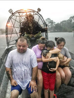 In this photo provided by the Texas Parks & Wildlife Department, a family is rescued via fan boat by a member of the department from the flood waters of Tropical Depression Imelda near Beaumont, Texas, Thursday, Sept. 19, 2019. (Texas Parks & Wildlife Department via AP)
