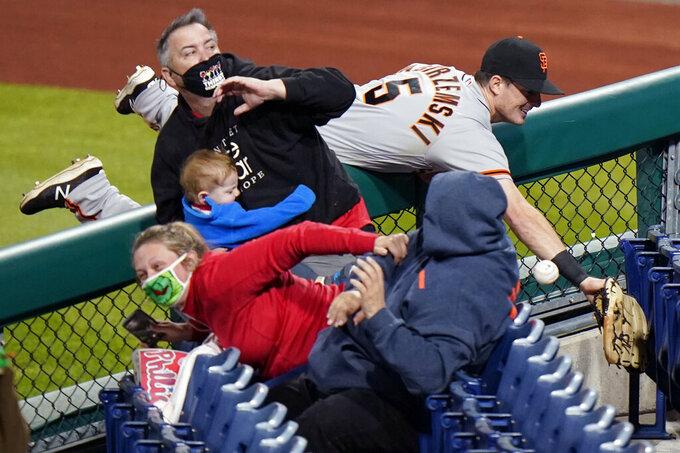 San Francisco Giants right fielder Mike Yastrzemski cannot reach a pop foul ball by Philadelphia Phillies' Rhys Hoskins during the ninth inning of a baseball game, Tuesday, April 20, 2021, in Philadelphia. (AP Photo/Matt Slocum)