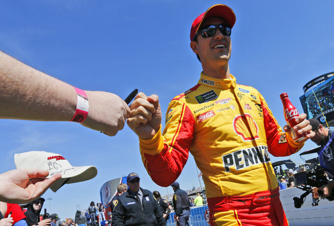 Joey Logano fist-bumps a fan during driver introductions prior to a NASCAR Cup Series auto race at Martinsville Speedway in Martinsville, Va., Sunday, March 24, 2019. (AP Photo/Steve Helber)
