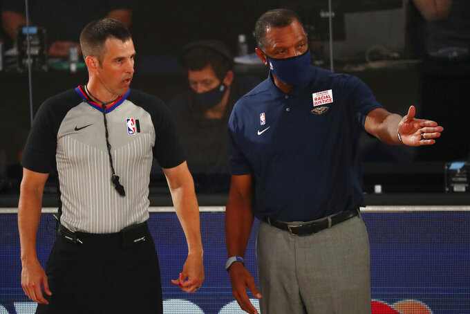 New Orleans Pelicans head coach Alvin Gentry, right, talks with an official during the first half of an NBA basketball game against the Orlando Magic, Thursday, Aug. 13, 2020, in Lake Buena Vista, Fla. (Kim Klement/Pool Photo via AP)