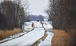 A rescue worker rides an ATV near the scene of a reported helicopter crash Thursday, Dec. 5, 2019, near Marty, Minn.  A Black Hawk helicopter with three crew members aboard crashed Thursday in central Minnesota, a state National Guard official said. (Dave Schwarz/St. Cloud Times via AP)