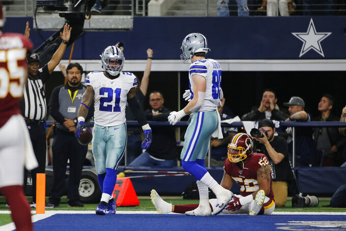 Dallas Cowboys running back Ezekiel Elliott (21) celebrates his touchdown catch against the Washington Redskins during the first half of an NFL football game in Arlington, Texas, Sunday, Dec. 15, 2019. (AP Photo/Michael Ainsworth)