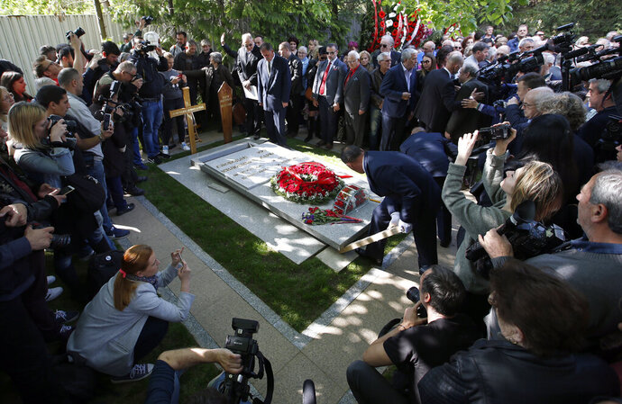 Workers place the stone onto the tomb of Mirjana Markovic, the widow of former strongman Slobodan Milosevic during her funeral at the yard of his estate in his home town of Pozarevac, Serbia, Saturday, April 20, 2019. Markovic died last week in Russia where she had been granted asylum. The ex-Serbian first lady had fled there in 2003 after Milosevic was ousted from power in a popular revolt and handed over to the tribunal in The Hague, Netherlands. (AP Photo/Darko Vojinovic)