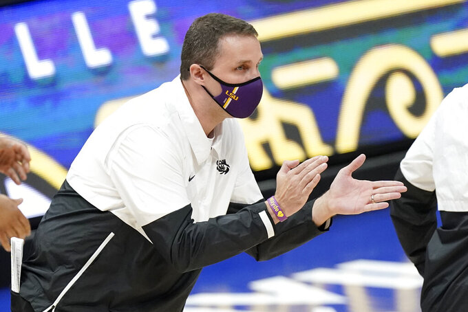 LSU head coach Will Wade applauds his team in the first half of an NCAA college basketball game against Mississippi in the Southeastern Conference Tournament Friday, March 12, 2021, in Nashville, Tenn. (AP Photo/Mark Humphrey)