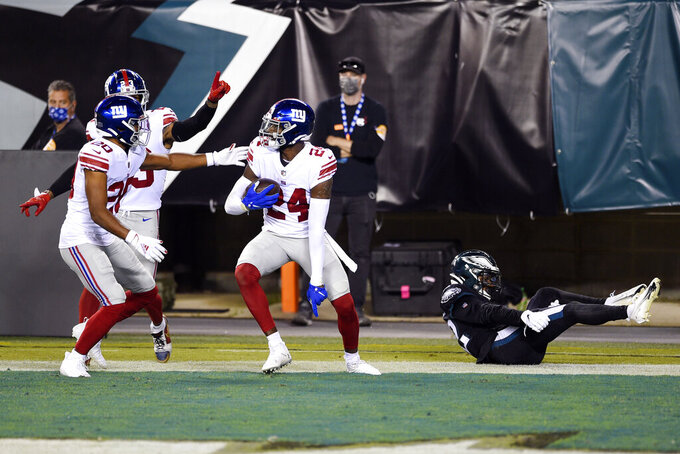 New York Giants' James Bradberry (24) reacts with teammates after intercepting a pass during the first half of an NFL football game against the Philadelphia Eagles, Thursday, Oct. 22, 2020, in Philadelphia. (AP Photo/Derik Hamilton)