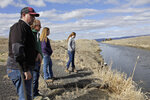 In this  March 2, 2020, hoto, farmer Ben DuVal; his wife, Erika, and their daughters, Hannah, 12, in purple, and Helena, 10, in gray, stand near a canal for collecting run-off water near their property in Tulelake, Calif. Ben DuVal inherited the farm from his grandfather, a World War II veteran who won the land by lottery, and worries that plan to demolish four dams on the lower Klamath River could set a precedent for dam removal that could eventually threaten his livelihood. The proposal to remove the dams on California's second-largest river to benefit threatened salmon has sharpened a decades-old dispute over who has the biggest claim to the river's life-giving waters. (AP Photo/Gillian Flaccus)