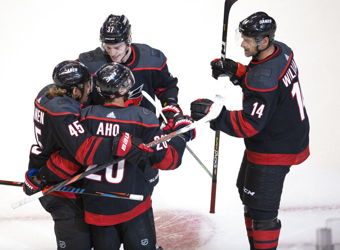 Carolina Hurricanes center Sebastian Aho (20) celebrates his goal with teammates Sami Vatanen (45), Andrei Svechnikov (37) and Justin Williams (14) during the second period against the New York Rangers in the NHL hockey Stanley Cup playoffs in Toronto, Saturday, Aug. 1, 2020. (Frank Gunn/The Canadian Press via AP)