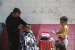 A barber cuts a child's hair at the Kiki Romero Sports Complex migrant shelter in Ciudad Juarez, Mexico, Wednesday, April 21, 2021. Mexico said it is planning to set up 17 shelters for underage migrants along the country's southern border, as well as some along the northern border with the United States, amid a wave of child migrants coming from Central America. (AP Photo/Christian Chavez)