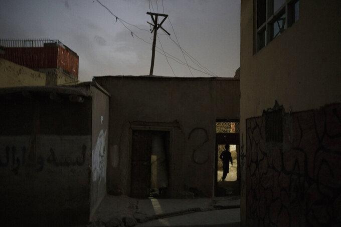 A boy walks into his house as the night falls in Kabul, Afghanistan, Saturday, Sept. 11, 2021. (AP Photo/Felipe Dana)