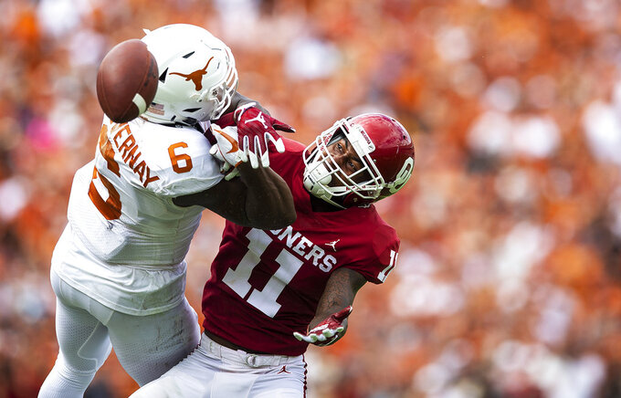 FILE - In this Oct. 6, 2018, file photo, Oklahoma cornerback Parnell Motley (11) contests a pass intended for Texas wide receiver Devin Duvernay (6) during an NCAA college football game at the Cotton Bowl in Dallas. No. 5 Oklahoma and No. 9 Texas are playing in a rare Red River rivalry rematch in the Big 12 championship game on Saturday. It is the first time in 115 years that the border state rivals will play twice in the same season.   (Nick Wagner/Austin American-Statesman via AP)
